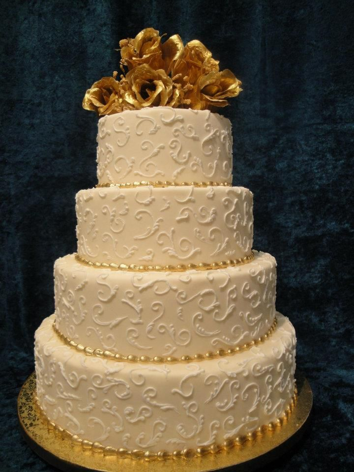 Custom four-tier white and gold wedding cake. Swirl design with gold ...
