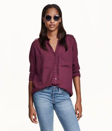 En rett skåret, v-ringet bluse i vevd kvalitet. Blusen har knapping foran og skulderklaffer med knapp. Brystlommer. Lange ermer som kan festes opp med bånd og knapp.