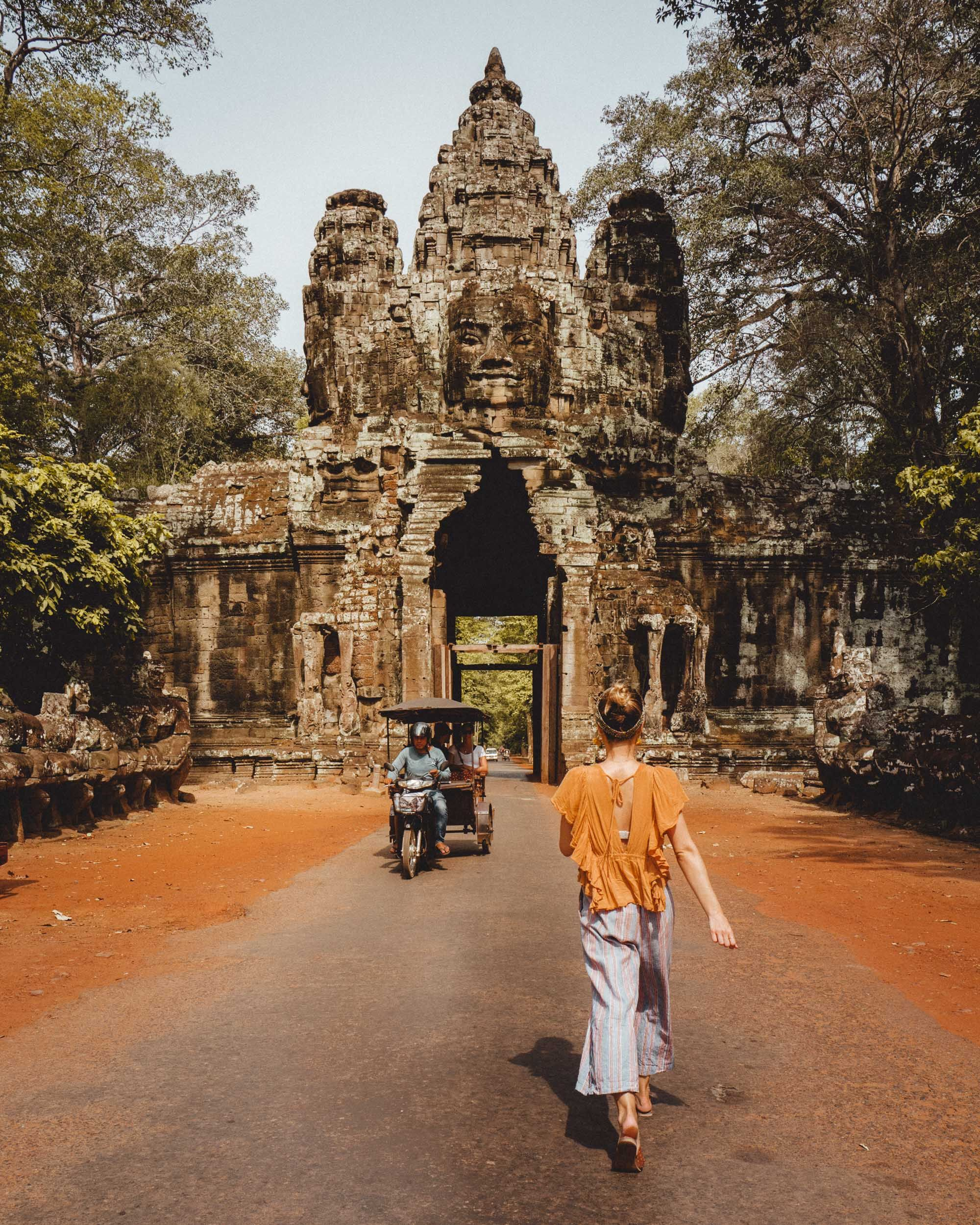 Bayon temple entrance with tuk tuk in Angkor Wat Cambodia via @finduslost | The Angkor Wat temple in Siem Reap, Cambodia is one of the most ancient temples in the entire world and should be at the top of any Southeast Asia travel itinerary. Click through to read the complete guide. #angkorwat #siemreap #cambodia #southeastasia #temples #finduslost