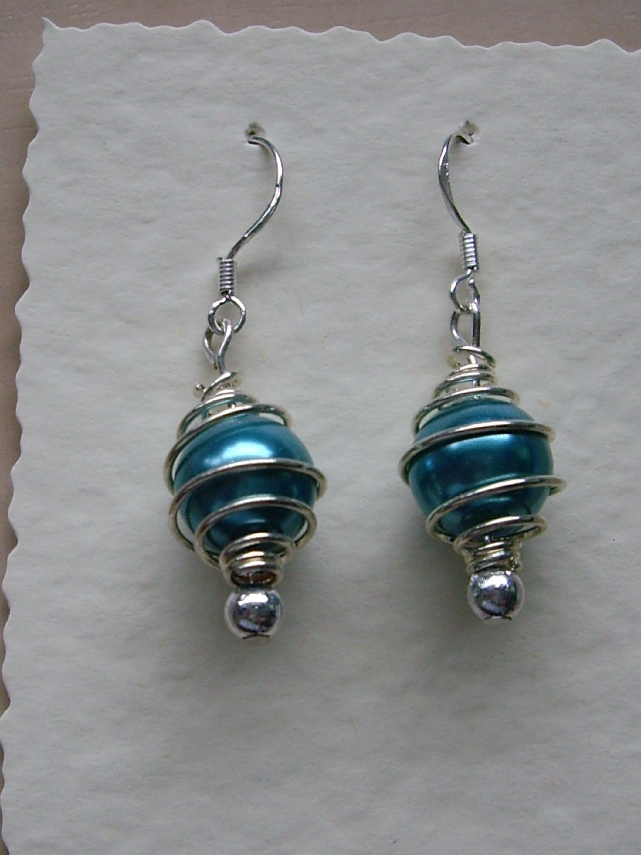 Sterling Silver Ear Wires with a silver plated cage containing a deep turquoise glass pearl. A small silver bead completes the earring
