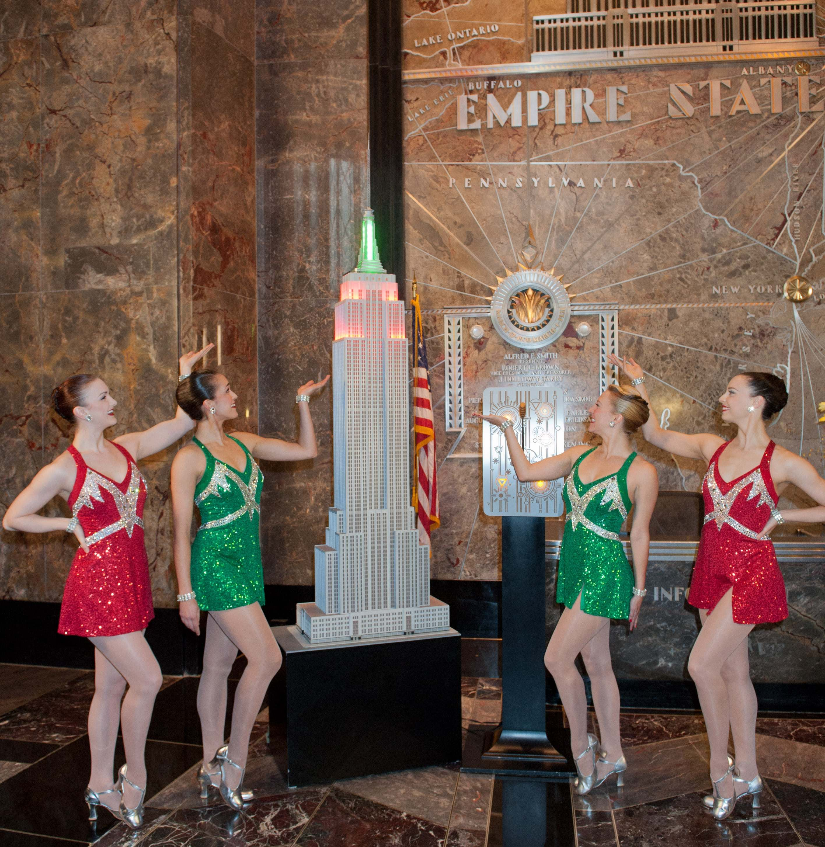 The Radio City Rockettes light the Empire State Building in red and