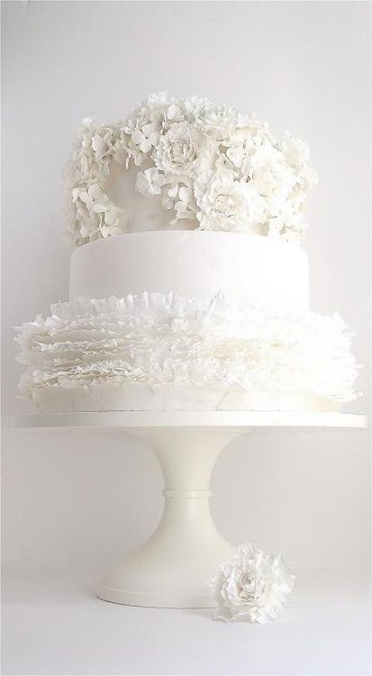 White Ruffled Wedding Cake topped with Delicate White Flowers