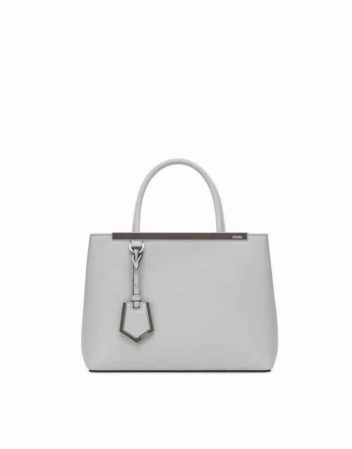 88d6825e15  Small  tote  bag with button clasp and double handle. Interior with  zippered partition that divides it into two compartments. Detachable  shoulder strap.