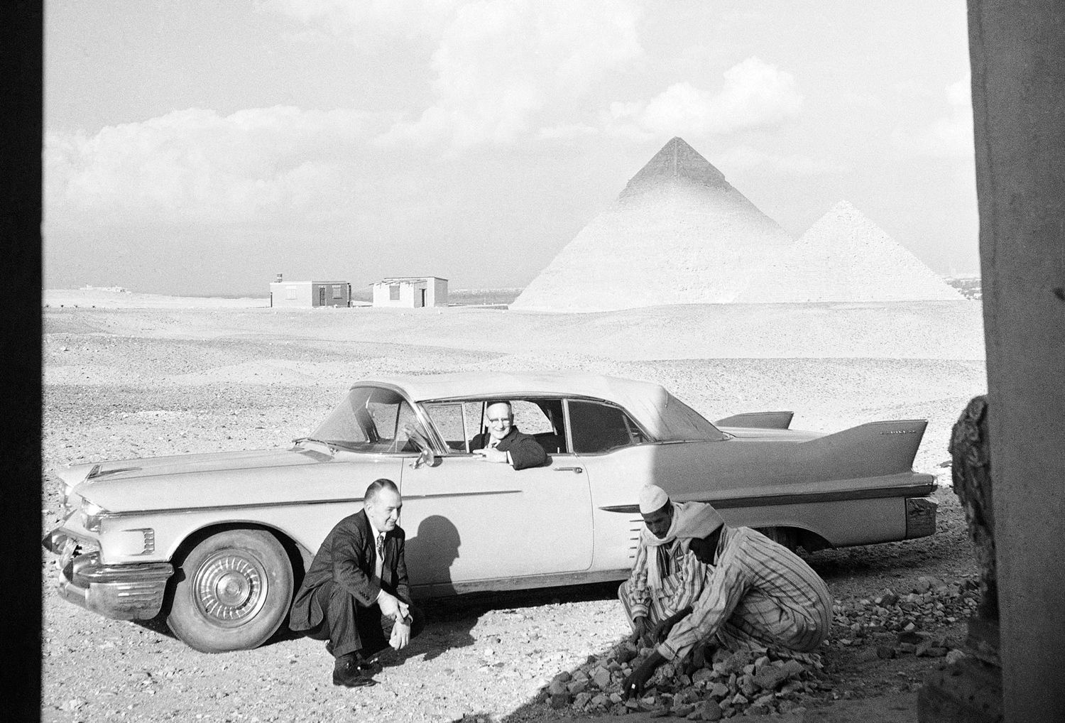 """From their Cadillac, Jack Carrigan (inside car) and Louis Miller Bailey, watch their two Egyptian servants clear away small stones in front of their retirement home at Giza, Egypt, on February 16, 1965. In the background are the famed 3,500-year-old pyramids which are their neighbors. The two men retired from Hollywood, California, to Egypt because they were tired of the film capital's """"lurid industrialization."""""""
