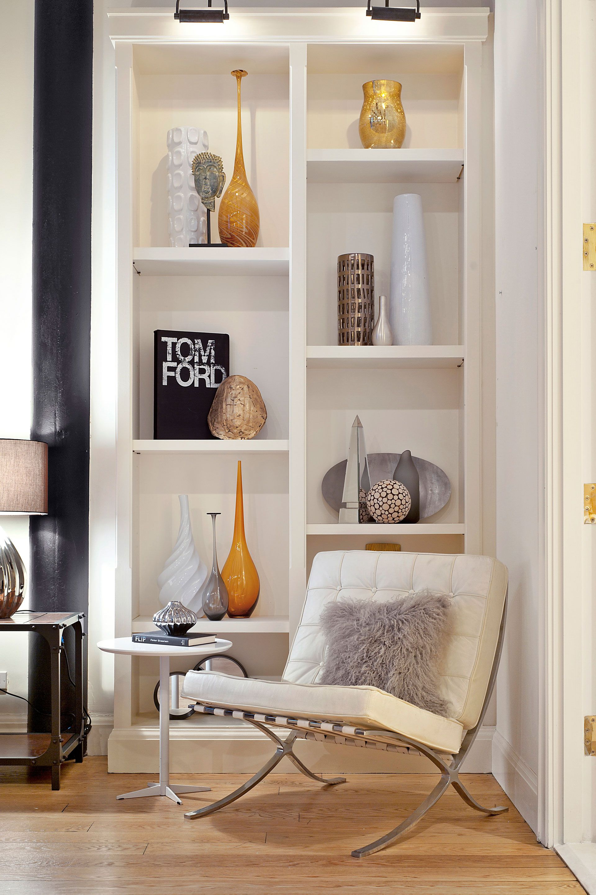 """Rather than jamming shelves full of knickknacks, Eisen opted for a minimalist look: Several books stand upright along with tall vases that fill the space without overcrowding it. She also added objects of various height and color to give the bookcase personality. Her favorite part about decorating this home? """"Turning wasted, unused space into a functional reading nook that can be enjoyed by many by simply adding a chair."""" Steal this look with clusters of tall, affordable vases.   - ..."""