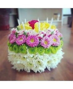 A cake made with fresh flowers and small candles are on top to
