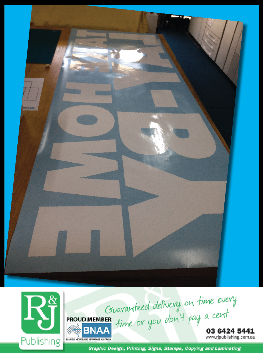 Vinyl lettering being prepared for a window.