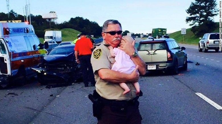 Officer comforts baby at the scene of a crash in Alabama