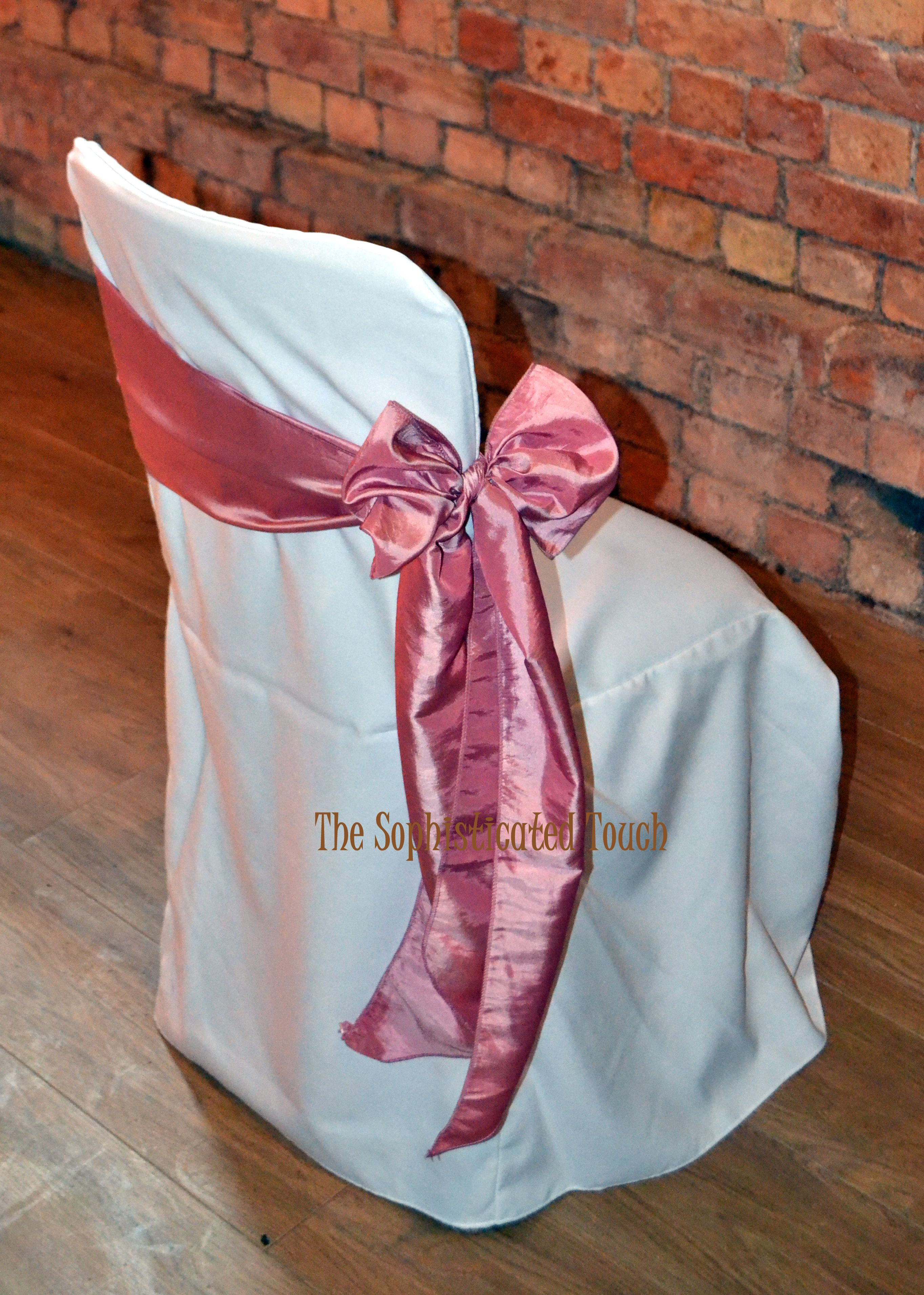 Dusky pink satin side bow on white chair cover with