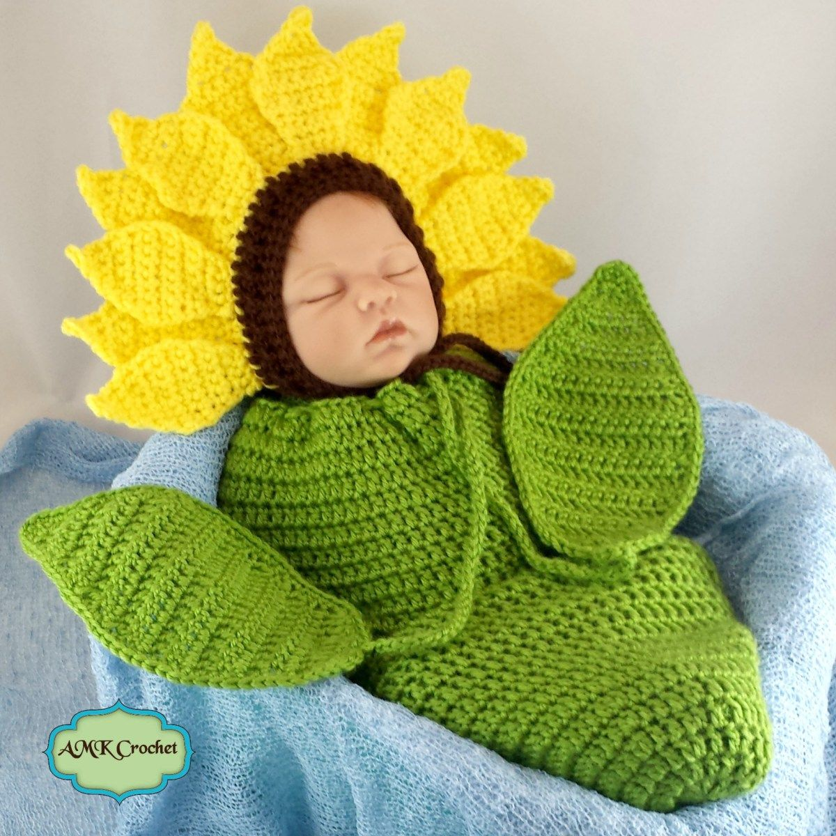 Crochet Newborn Sunflower Bonnet Hat with Cocoon Photo Prop Pattern by  AMKCrochet.com. Leaves attached to the ties of the swaddle sack 927f5259ef50