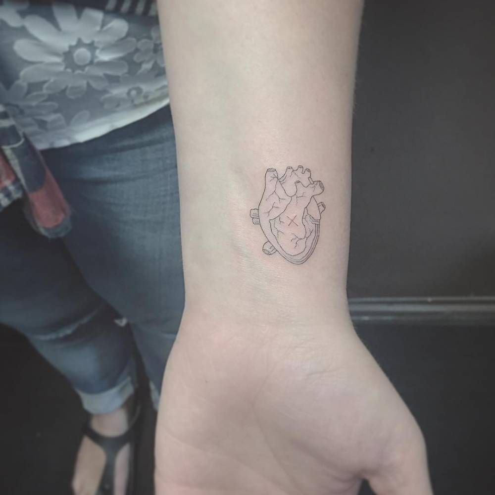 Fine line style heart tattoo on the left inner wrist