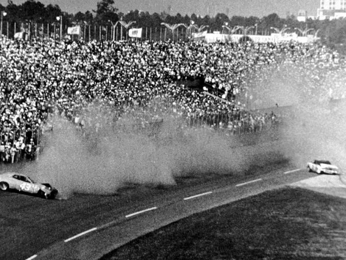 In one of the most famous crashes in NASCAR history, David Pearson and Richard Petty wreck while racing for the lead on the final lap of the 1976 Daytona 500.