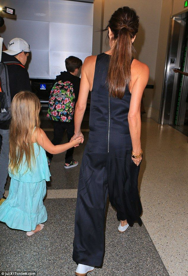 Jetting out: Victoria was the doting mother as she held hands with her youngest child...