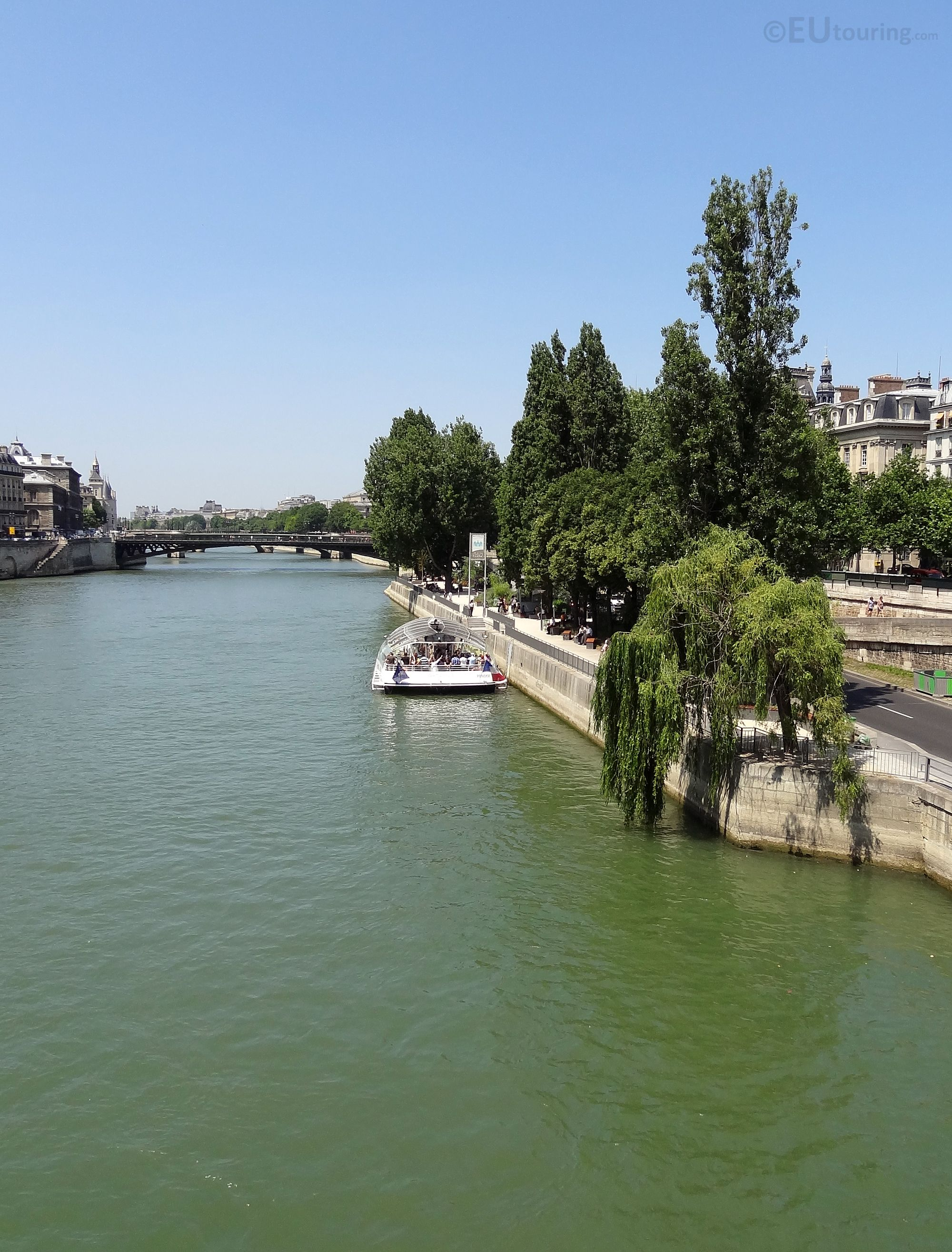 This photo shows just how peaceful and near-empty the River Seine can be at times, a lone tour boat going along the side of the tree lined river in Paris.  More information and details at www.eutouring.com