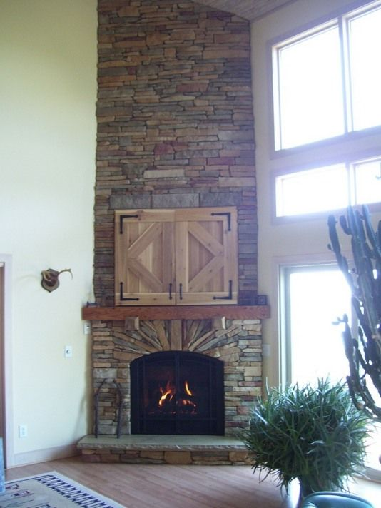 Extra high ceiling corner stacked stone fireplace cabin for Corner fireplace stone