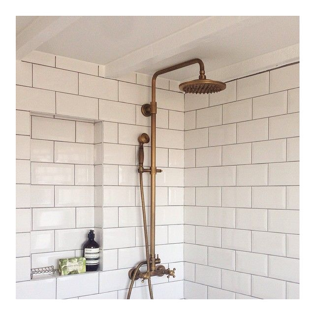 Exposed wooden ceiling beams, antique brass fittings, an open wet room shower and afternoon light