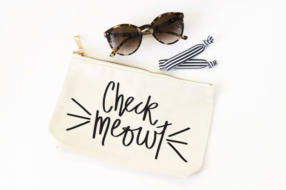 """Keep your make up and jewelry essentials organized with our """"Check Meowt""""  canvas cosmetic bag!  :: 9.75"""" W x 6"""" H :: Natural canvas color :: Made of 100% cotton canvas :: Gold zipper and hardware :: Available with or without white silky lining :: Care: spot clean with mild soap and water :: Black hand lettered text to read """"Check Meowt"""""""