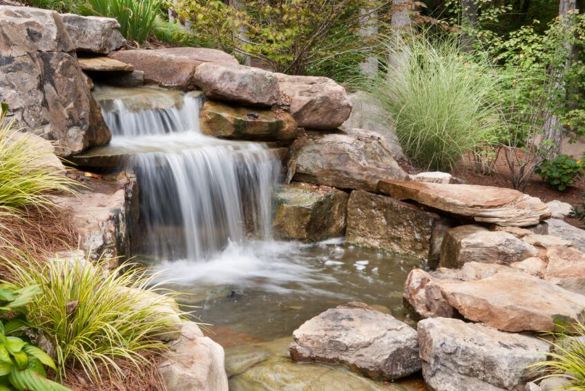 The Easiest Way To Make A Garden Waterfall Look And Feel Natural Is To Surround The Entire Water Features In The Garden Waterfalls Backyard Outdoor Waterfalls