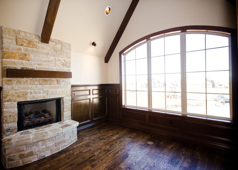 Arch Top Windows Stone Fireplace Dark Wood Floors Wood
