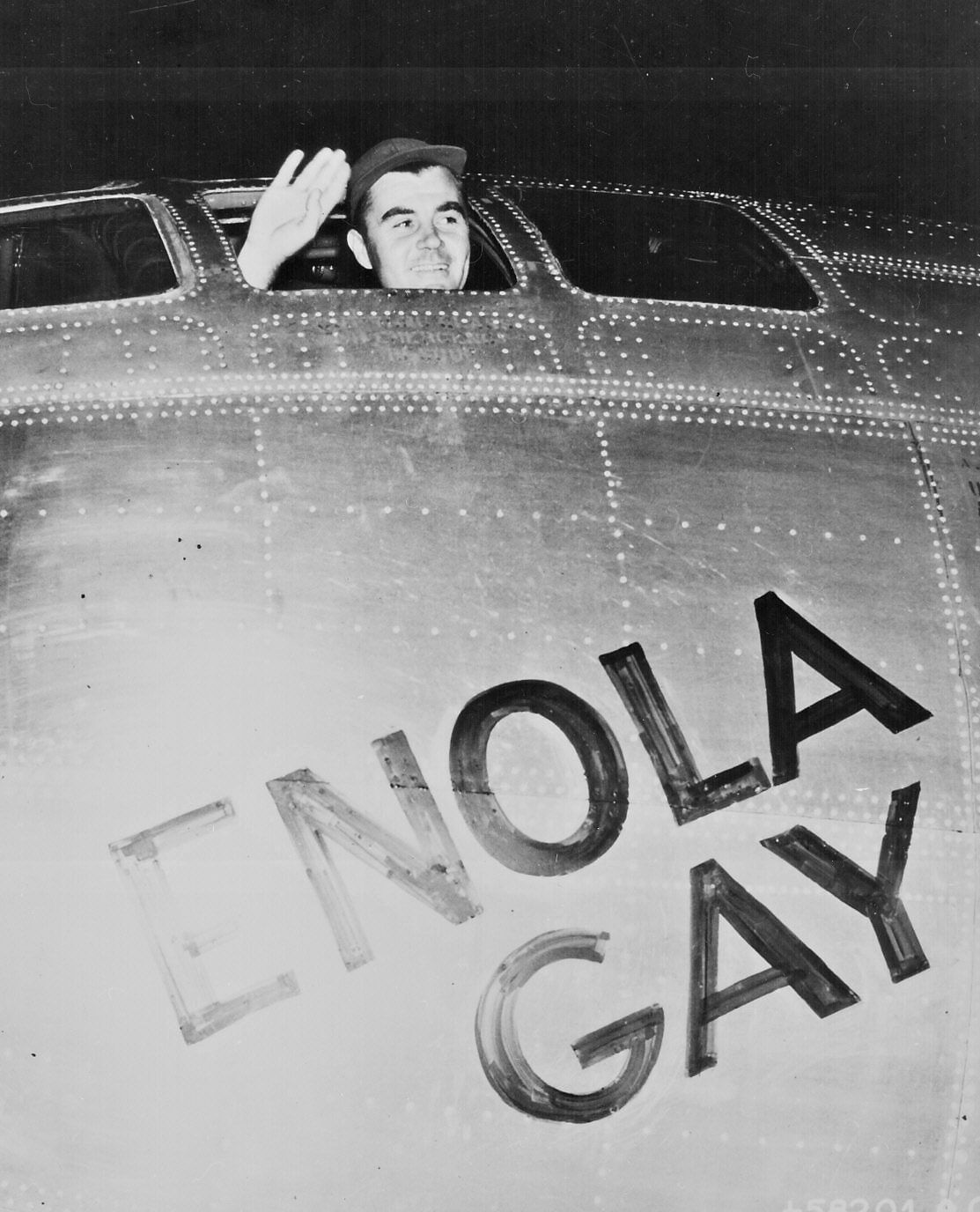 """""""Col. Paul W. Tibbets, Jr., pilot of the ENOLA GAY, the plane that dropped the atomic bomb on Hiroshima, waves from his cockpit before the takeoff, 6 August 1945."""""""