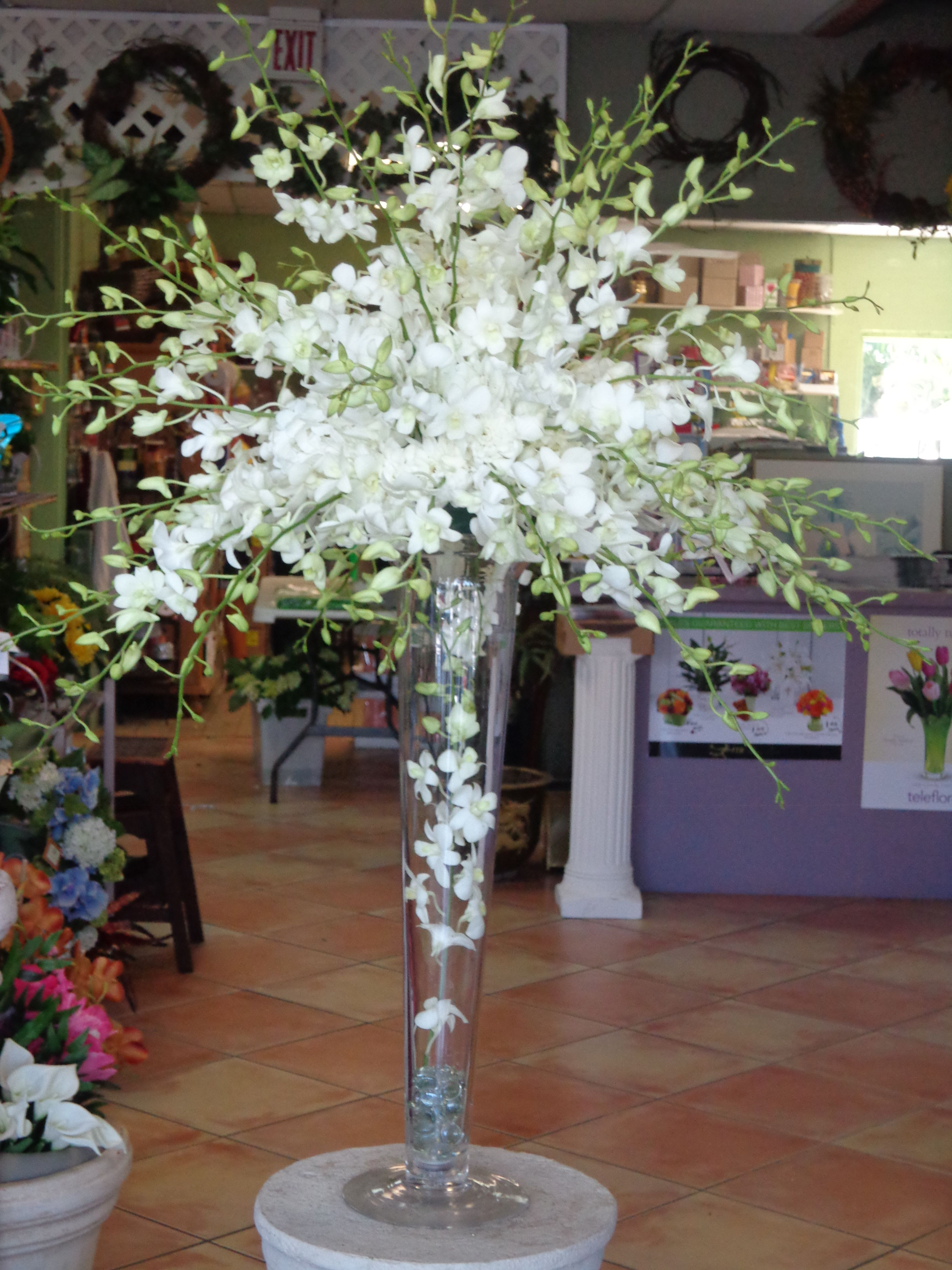 Centerpiece Of White Dendrobium Orchids On A Trumpet Vase