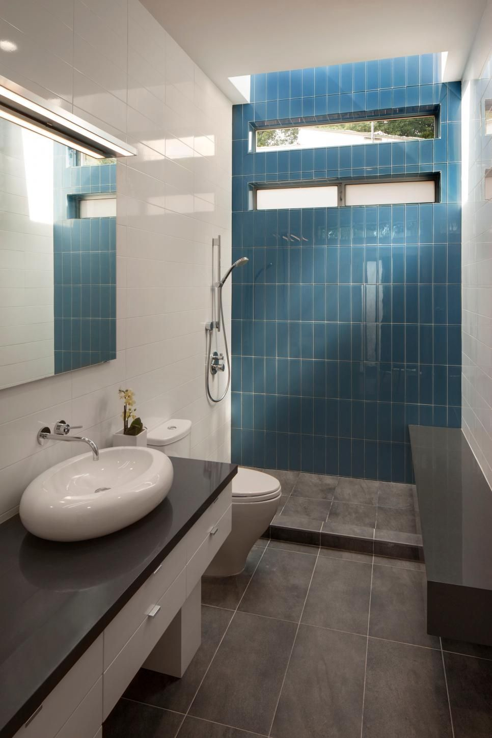 A bright blue tile accent wall at the back of the shower Bright blue tile