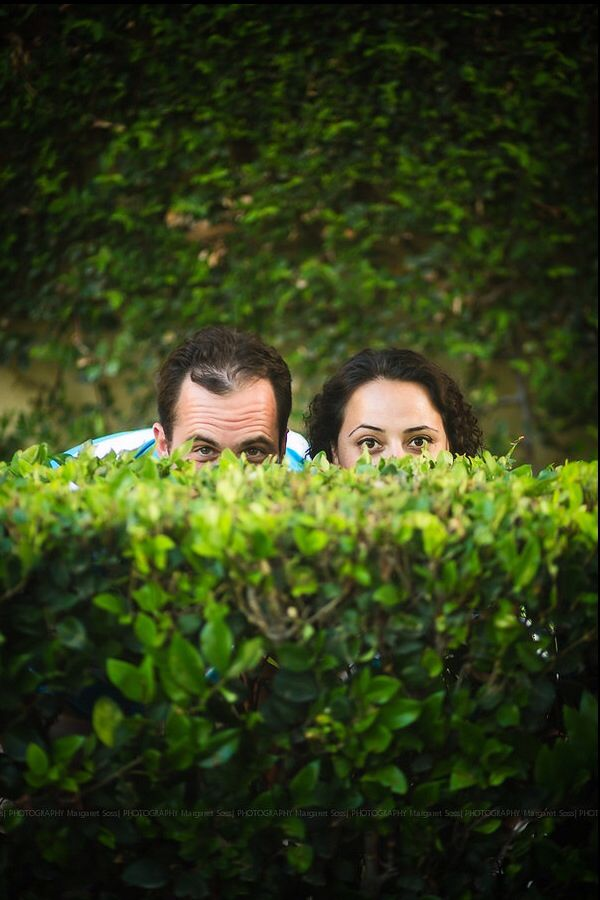Engagement photo of a cute couple hiding behind a bush. Orange ...