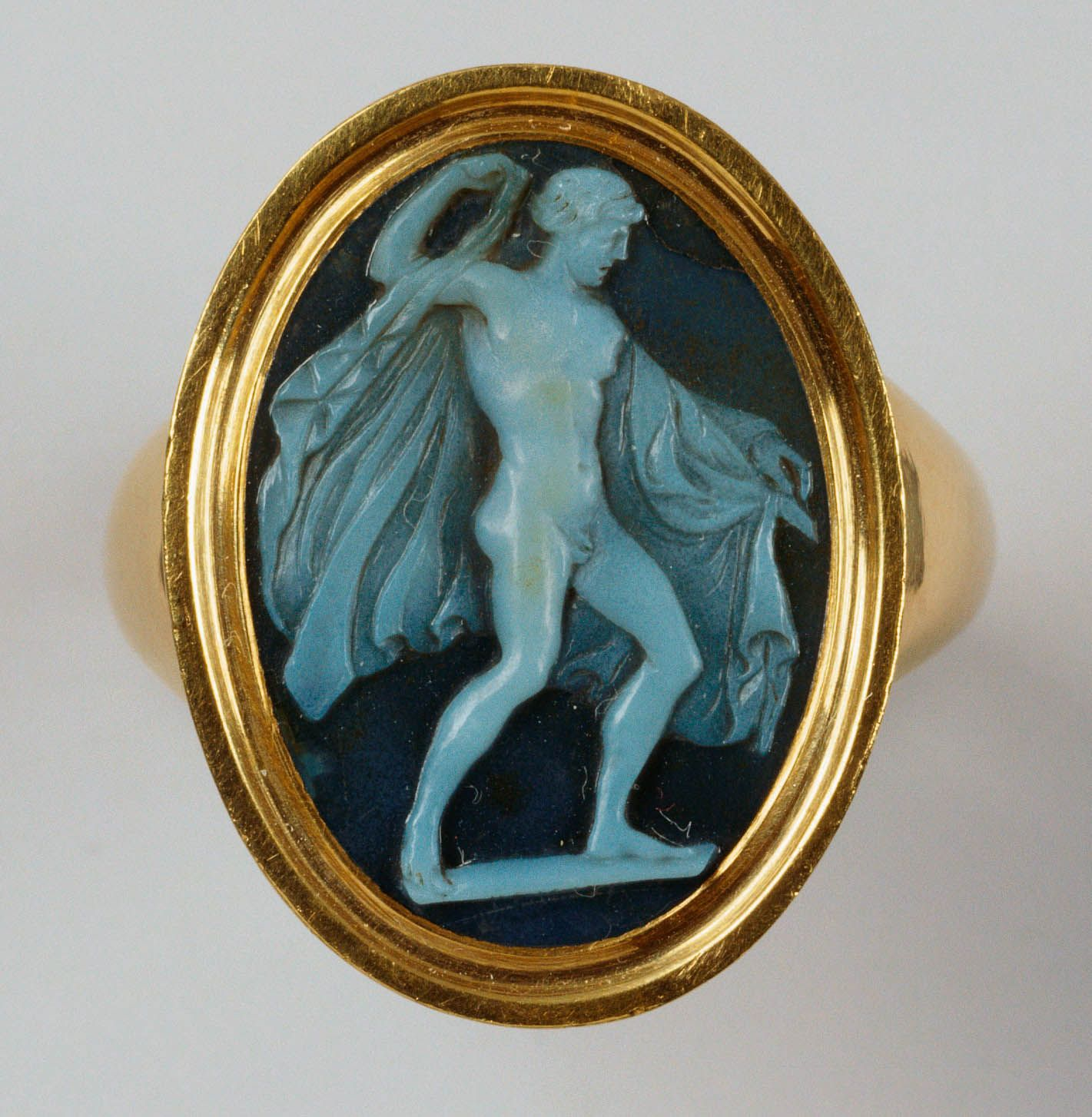 Cameo of a full-length naked figure of the god of wine, Dionysus, dancing, in three-quarter view, with his head in profile to the right. A cloak is draped over his left arm and held in his raised right hand. English, cameo 18th century, ring late 18th century, onyx and gold