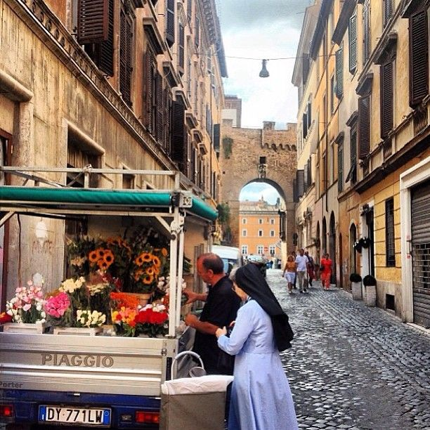 """A flower stand (""""carretto dei fiori"""") nestled in the charming, cobbled backstreets of Rome."""