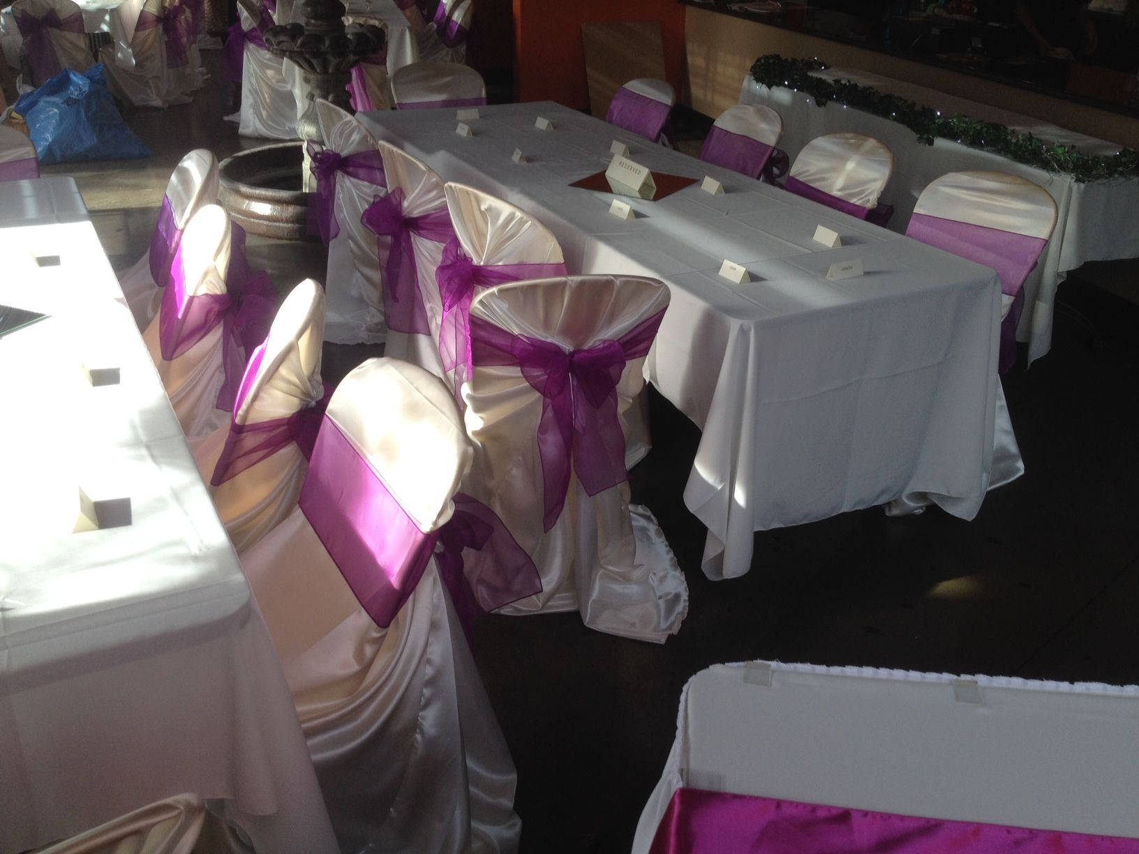 The universal chair cover in off white satin fabric with purple