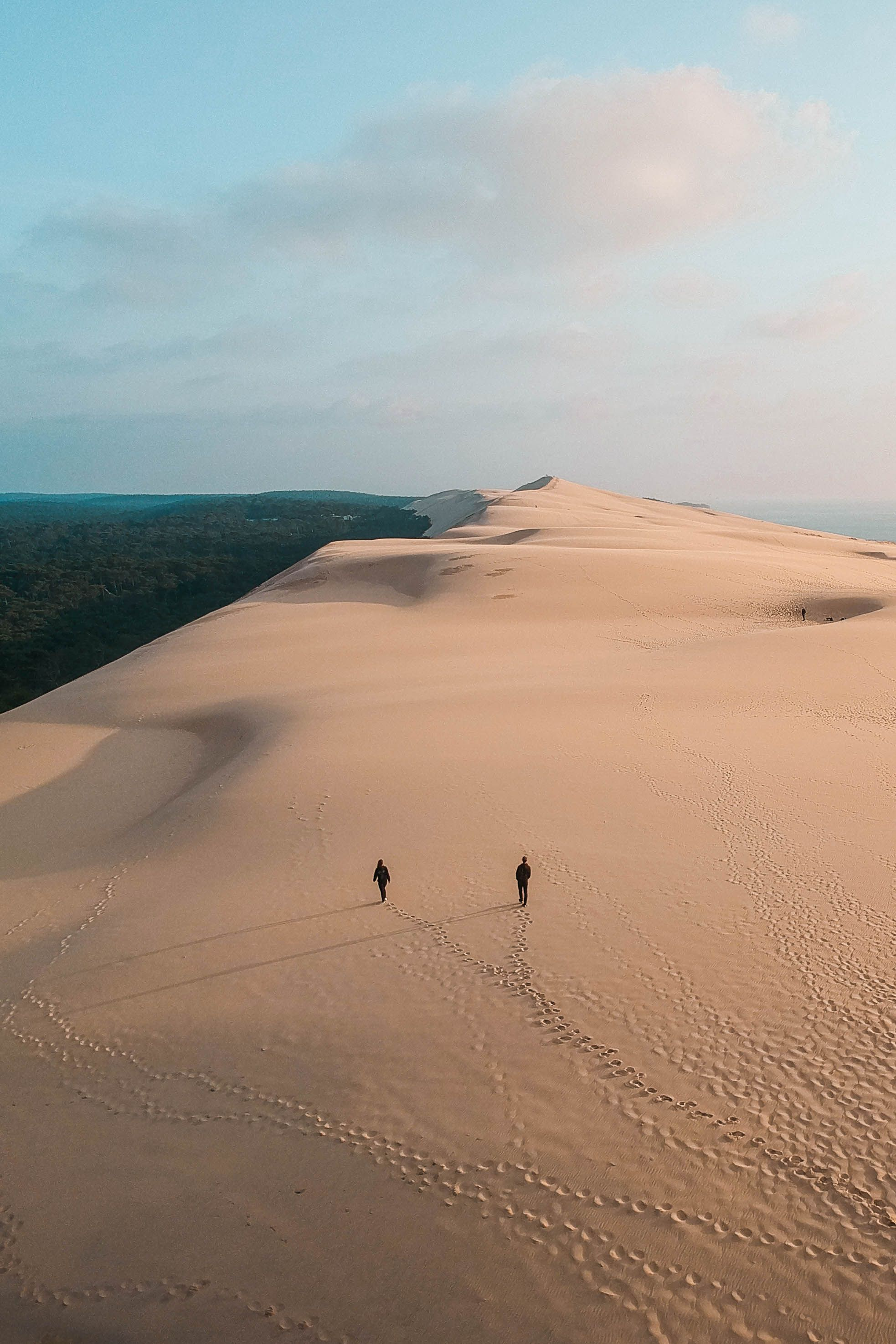 Dune du Pilat is the highest sand dune in Europe located in South-West France. It's a unique travel destination and should be on everyone's travel bucket list! Dune du Pilat is easy to get to from Bordeaux or Arcachon Bay. #travelblog #visitfrance #travelcouple #beautifuldestinations #instagrammableplaces #bucketlisttravel #summerdestinations #europetravel #droneshots