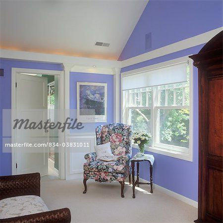 SITTING ROOM - Upholstered wing chair, floral print, sitting area in bedroom, double hung windows, shade, indirect lighting in architectural features, periwinkle blue walls and white trim  – Image © Sheltered Images / Masterfile.com: Creative Stock Photos, Vectors and Illustrations for Web, Mobile and Print