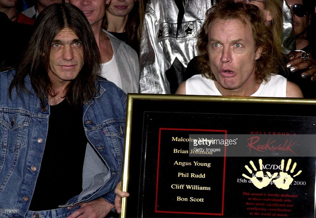 Guitarist Angus Young of the Australian rock band AC-DC, right, holds plaque as brother and bandmate Malcolm Young looks on after the Rock Walk handprint ceremony September 15, 2000 at the Guitar Center in Hollywood, Ca.