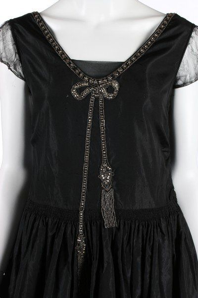 A black taffeta robe de style, circa 1926, with rhinestone and seed-beaded trompe l'oeil bow to the bodice front, shirring to waist, tulle puff sleeves, the hem faced in ivory taffeta, with integral black taffeta hooped panniers, bust 92cm, 36in; together with a dark brown satin dress c.1918-20, labelled 'Ferle Heller', with tiered skirt and trimmed with ribbons (2)