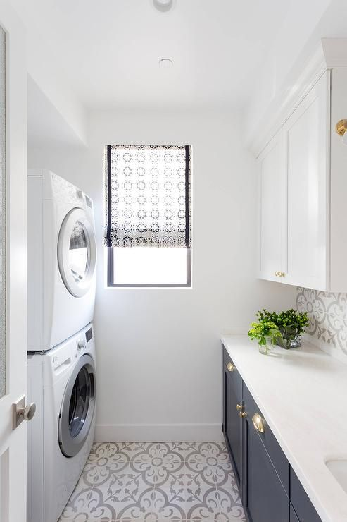 Small Blue And White Laundry Room Features A Stacked Washer Dryer Placed On Granada Normandy Tiles Facing Upper Cabinets Mounted Above Dark