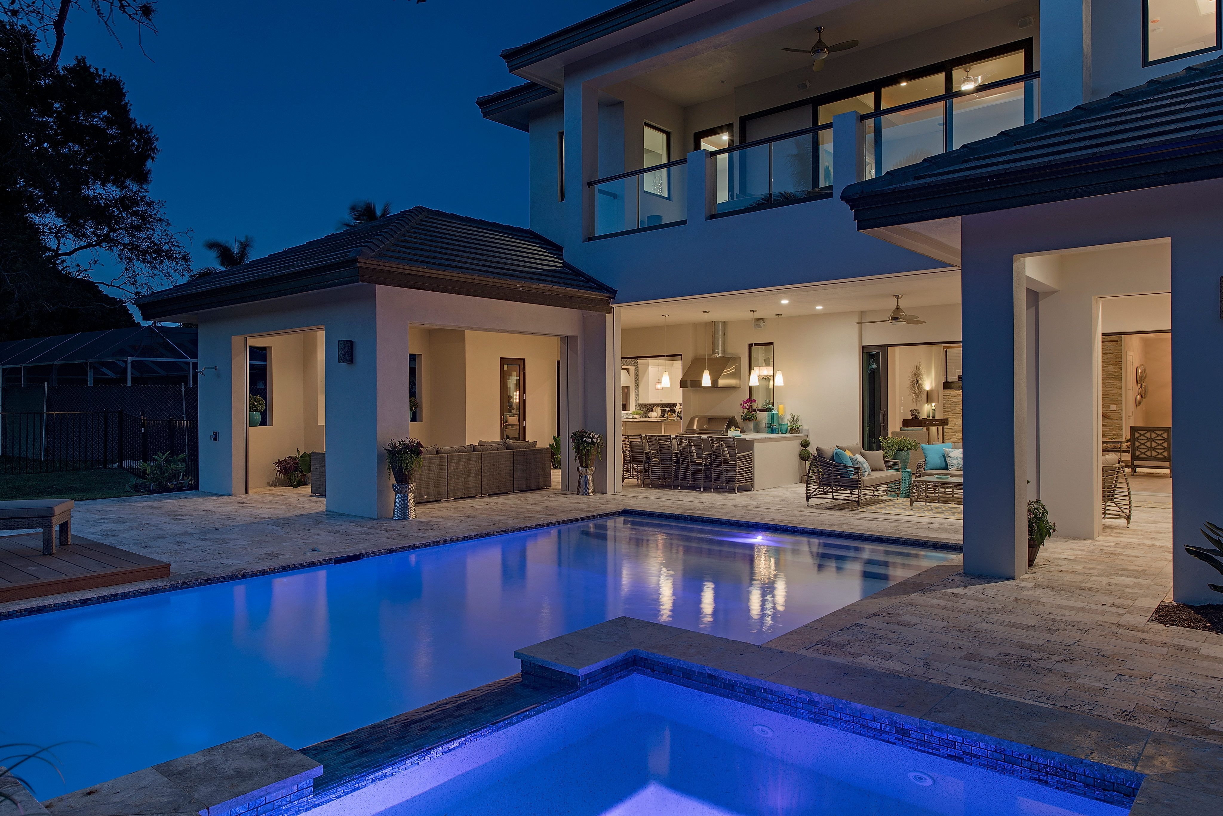 Infinity pool and spa rear elevation at dusk home custom for Pool design naples fl