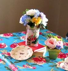 Sweet 16 Vintage Alice in Wonderland Tea Party Birthday Party--The tables are all set (close-up of table decor).  We decoupaged (clean) large tomato juice cans with vintage images we had found on the internet and filled them with artificial floral arrangements.