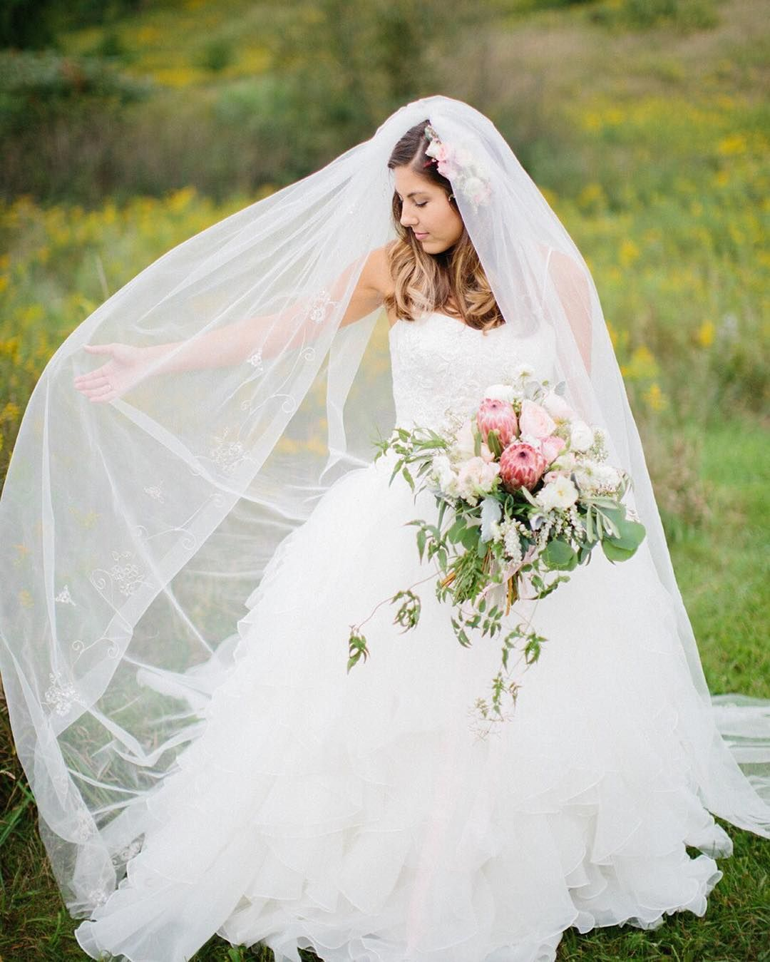 A bridal ball gown and cathedral veil make for a classic