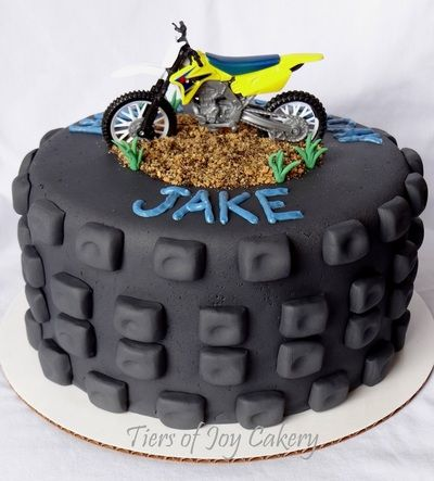 Motorcycle tire cake with toy motorcycle on top.