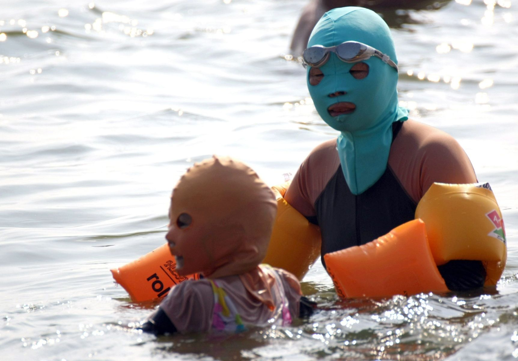 In China, where sun tan is negatively stigmatized, beach goers wear masks.
