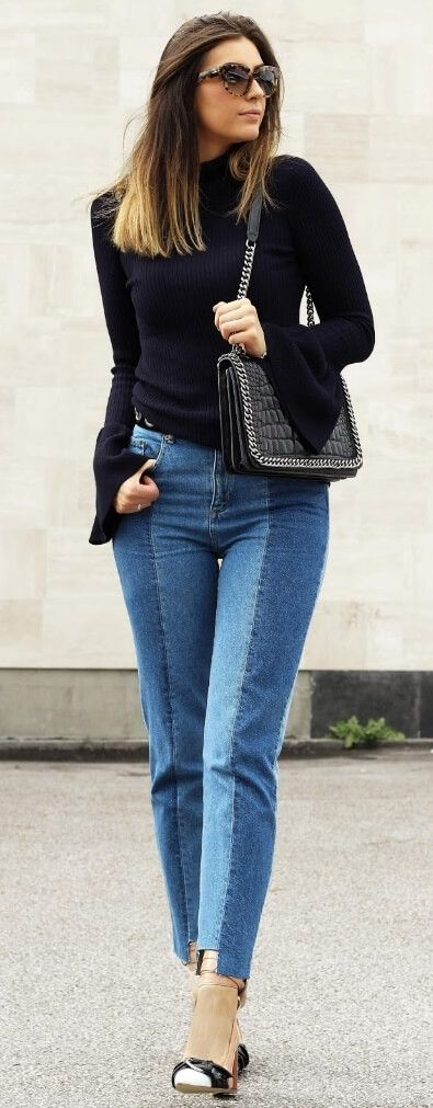 df49b7d4c4dff Fashionable woman is wearing patchwork denim jeans and a turtleneck sweater  with bell sleeves. The season s trendiest styles go together ever-so-well   ...
