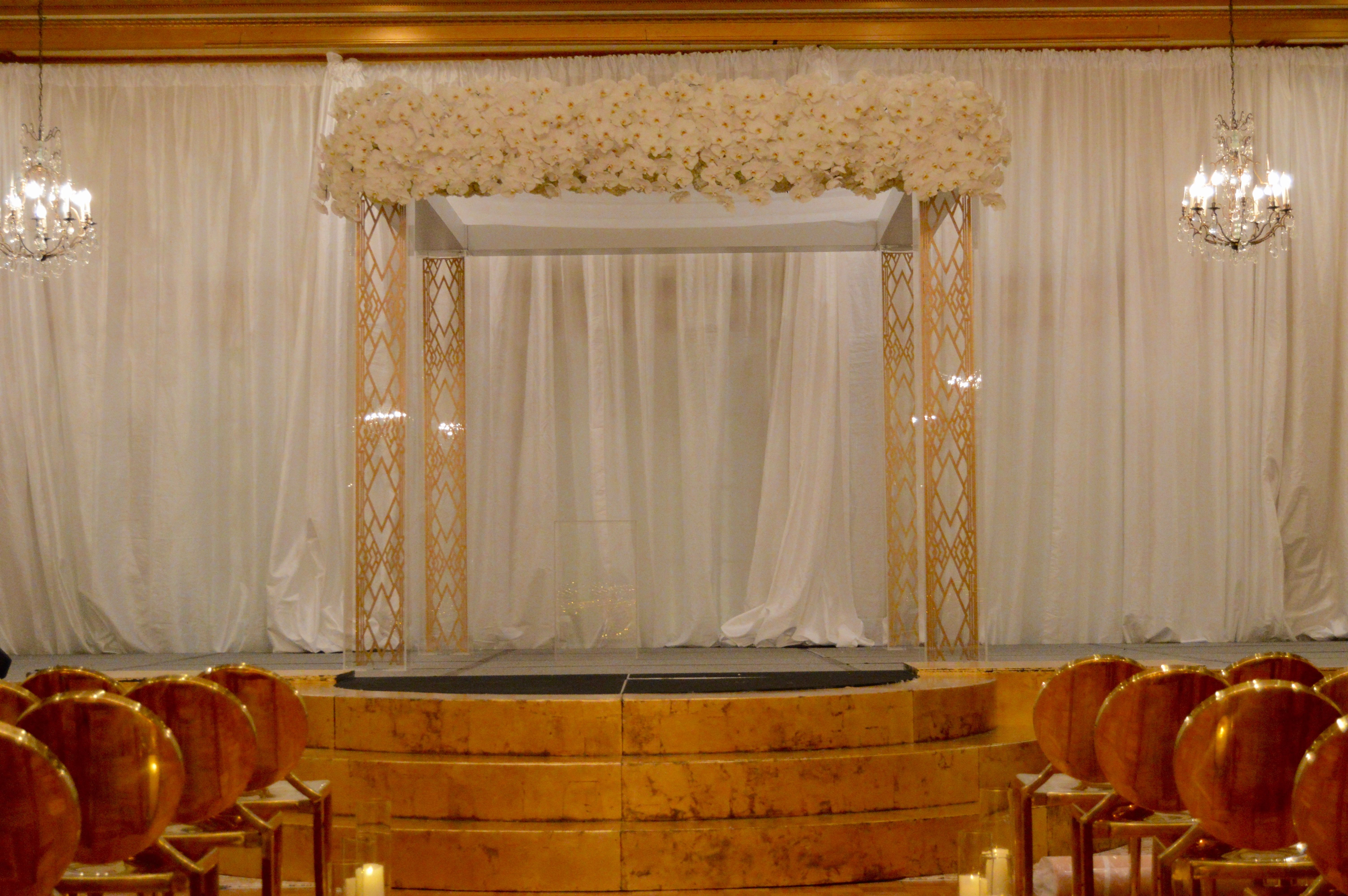 Acrylic let Chuppah with suspended art deco panels within the legs. Solid white phalenopsis orchid florals along the top. Flanked with golden round steps and our gorgeous Midas chairs. Decadence within the world famous Peabody!