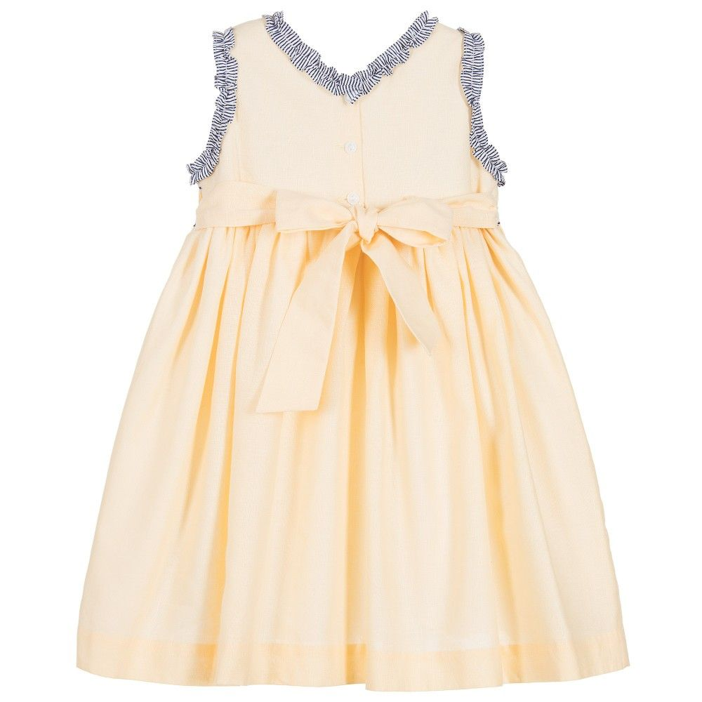 Girls yellow, sleeveless dress and hairband set byPretty Originals, with striped trim. Made in soft woven linen, fully lined, with back buttonfastening. It has abeautiful hand smocked bodice, with embroidery, and a sash belt that ties at the back. The full skirt has gathering from the high waist and it comes with a matching elasticated hairband.