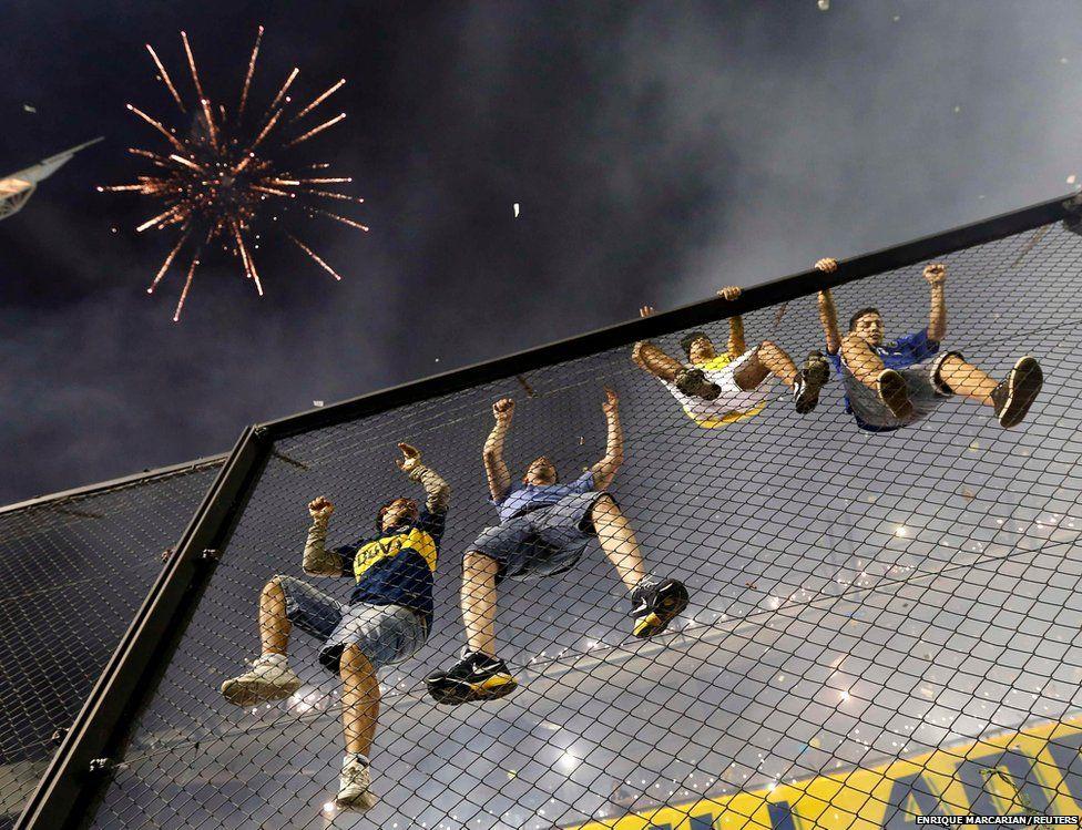 Boca Juniors fans climb a fence
