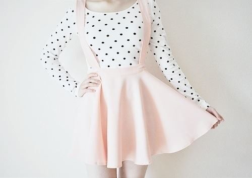 A cute classic look with a white shirt with black polka dots and a pink suspender skirt.