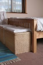 How about some neat laundry baskets or linen storage baskets at the foot of the bed!