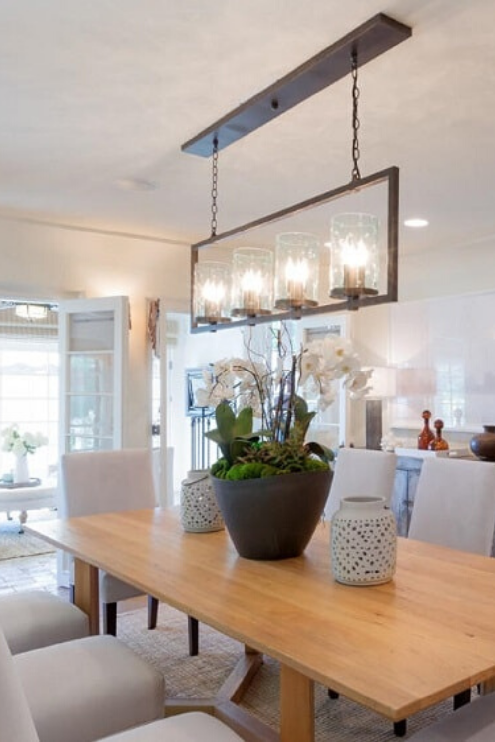 This modern dining room has modern design and simple yet stylish decor. There's a large rectangular wooden dining table surrounded by beige cushioned chairs and topped with decorative lighting that contrasts the ceiling. #DiningRoomDecor #DiningRoomIdeas #DiningRoomDesign  Courtesy of TopTenRealEstateDeals.com