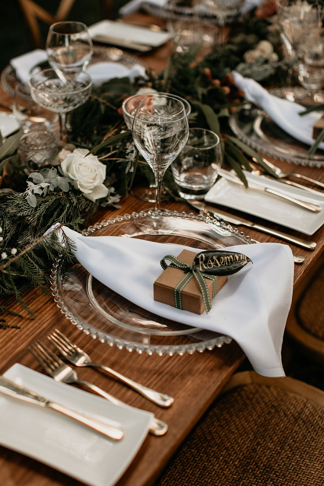 Boho wedding reception with glass plates, green leafy