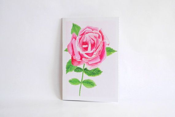 Do you prefer gorgeous blooms to the lush greens of cacti and succulents? This A5 notebook is decorated with a solitary rose, pretty in pink against a pale blush background. The design is derived from an original watercolour illustration. The eco-friendly notebook is made from recycled paper and card stocks and you can choose from a selection of plain, lined, dotted or squared pages for all your writing, sketching and planning needs. OVERVIEW ✎ This item is ready-to-ship and will be disp...