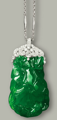JADEITE AND DIAMOND PENDANT NECKLACE The highly translucent jadeite plaque of intense emerald green colour, carved as a lotus leaf and fruits, highlighted by a carved duck and frog, surmounted by a pear-shaped and brilliant-cut diamond-set clasp, accompanied by a link chain, mounted in 18 karat white gold, length approximately 510mm.